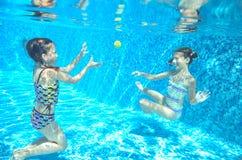 Los niños nadan en la piscina subacuática, las muchachas activas felices se divierten debajo del agua Imagen de archivo libre de regalías