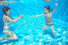 Los niños nadan en la piscina subacuática, las muchachas activas felices se divierten debajo del agua Fotografía de archivo
