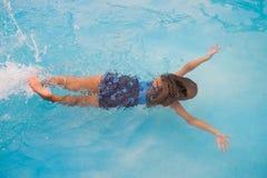 Los niños nadan en la piscina subacuática, las muchachas activas felices se divierten en agua Imagen de archivo