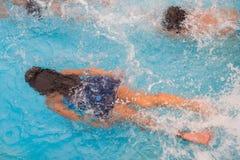 Los niños nadan en la piscina subacuática, las muchachas activas felices se divierten en agua Fotografía de archivo libre de regalías