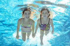 Los niños nadan en piscina bajo el agua, las muchachas se divierten en agua Foto de archivo libre de regalías