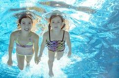 Los niños nadan en piscina bajo el agua, las muchachas se divierten en agua Imagenes de archivo
