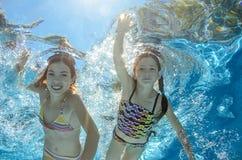 Los niños nadan en piscina bajo el agua, las muchachas se divierten en agua Imagen de archivo libre de regalías