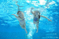 Los niños nadan en piscina bajo el agua, las muchachas se divierten en agua Fotos de archivo