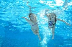 Los niños nadan en piscina bajo el agua, las muchachas se divierten en agua Imágenes de archivo libres de regalías
