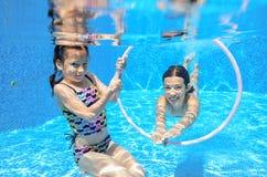 Los niños nadan en piscina bajo el agua, las muchachas se divierten en agua, Foto de archivo