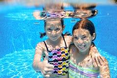 Los niños nadan en piscina bajo el agua, las muchachas se divierten en agua, Fotografía de archivo