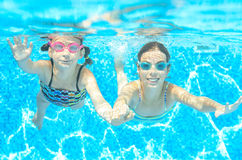 Los niños nadan en piscina debajo del agua, las muchachas activas felices en gafas se divierten, deporte de los niños Foto de archivo libre de regalías