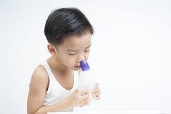 Los niños nasales limpian por la solución salina Imagenes de archivo