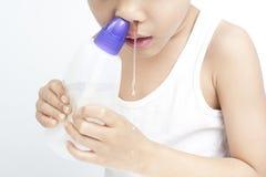 Los niños nasales limpian por la solución salina Fotos de archivo