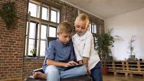 Los niños o los estudiantes sonrientes hermosos utilizan la tableta para aprender el nuevo programa de la programación informátic almacen de metraje de vídeo