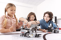 Los niños optimistas que trabajan en la tecnología proyectan en la escuela Imágenes de archivo libres de regalías