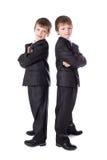 Los niños pequeños hermanan en la presentación de los trajes de negocios aislados en blanco Fotografía de archivo
