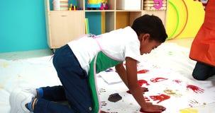 Los niños pequeños lindos dan la pintura en el Libro Blanco en sala de clase metrajes
