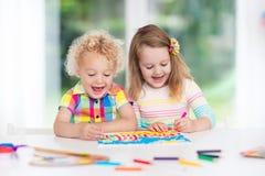 Los niños pintan y dibujan en casa fotografía de archivo