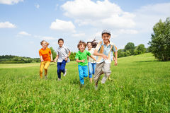 Los niños positivos juegan y corren juntos en el campo Fotografía de archivo