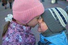 Los niños presionaron sus narices el uno al otro y mirando en sus ojos y sonrisa Imagenes de archivo