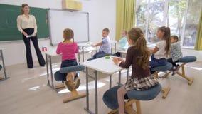 Los niños que aprenden, señora joven del profesor cerca de tablero conducen la lección cognoscitiva para los alumnos agradables e almacen de video