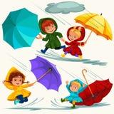 Los niños que caminan bajo llover el cielo con un paraguas, gotas de la lluvia están goteando en charcos, lloviendo el muchacho o Fotografía de archivo