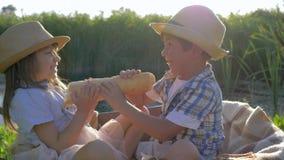 Los niños que comen el pan y se divierten que se sienta en carretilla en luz del sol en el tiempo del almuerzo durante día de fie almacen de metraje de vídeo