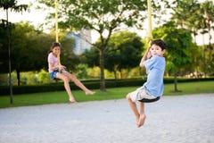Los niños que cuelgan en la suspensión rope en playgr Imagenes de archivo