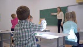 Los niños que enseñan, alumno en la lección escuchan el educador en la pizarra en enfocado en la sala de clase de la escuela almacen de metraje de vídeo