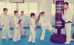 Los niños que entrenan a karate golpean con el pie en el saco de arena durante el cla del karate Fotos de archivo libres de regalías