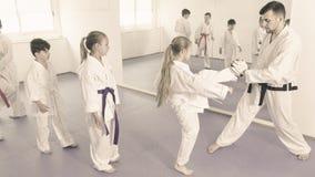 Los niños que entrenan a karate golpean con el pie en el saco de arena durante el cla del karate Fotografía de archivo