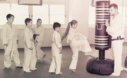 Los niños que entrenan a karate golpean con el pie en el saco de arena durante el cla del karate Imágenes de archivo libres de regalías