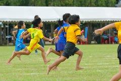 Los niños que hacen un trabajo en equipo corren la carrera en el día del deporte de la guardería Imagen de archivo