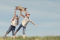 Los niños que juegan con cartulina juegan el aeroplano en el parque en t Imagenes de archivo