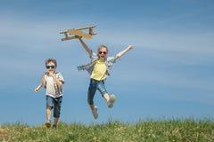 Los niños que juegan con cartulina juegan el aeroplano en el parque en t Foto de archivo libre de regalías