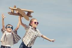 Los niños que juegan con cartulina juegan el aeroplano en el parque en t Fotos de archivo