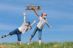 Los niños que juegan con cartulina juegan el aeroplano en el parque en t Fotos de archivo libres de regalías