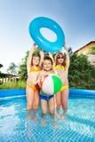 Los niños que juegan con la bola y la nadada del viento suenan en piscina Imagen de archivo libre de regalías