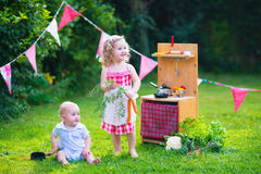 Los niños que juegan con una cocina del juguete en un verano cultivan un huerto Fotos de archivo