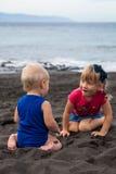 Los niños que juegan en la arena volcánica del negro de la arena del la de Playa varan Imagen de archivo libre de regalías