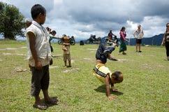 Los niños que juegan en la escuela colocan el trabajo en los headstands Imágenes de archivo libres de regalías