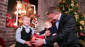 Los niños que miran los regalos de padres que el padre da a los hijos de un regalo de la Navidad, buen padre pasan Nochebuena con metrajes