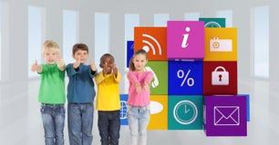 Los niños que muestran los pulgares suben gesto contra iconos del app Imagen de archivo