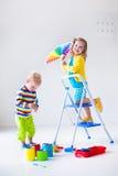 Los niños que pintan las paredes en casa remodelan Imagen de archivo libre de regalías