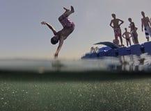 Los niños que saltan de la plataforma flotante del mar Fotos de archivo libres de regalías