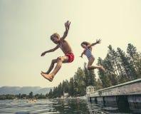 Los niños que saltan del muelle en un lago hermoso de la montaña Imagen de archivo libre de regalías