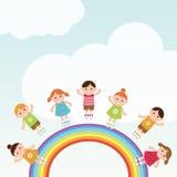 Los niños que saltan en el arco iris. Foto de archivo
