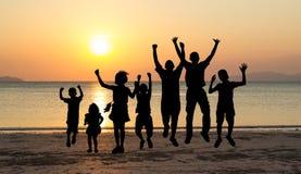 Los niños que saltan en el tiempo de la puesta del sol Fotos de archivo
