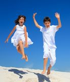 Los niños que saltan en la playa Fotos de archivo