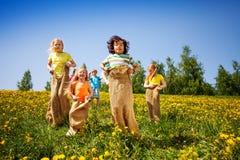 Los niños que saltan en los sacos que juegan juntos Imágenes de archivo libres de regalías