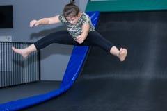 Los niños que saltan en los trampolines interiores se ríen Imagen de archivo