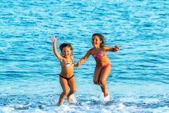 Los niños que saltan juntos en ondas Fotografía de archivo