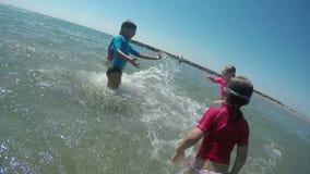 Los niños que saltan y que salpican en el mar almacen de metraje de vídeo